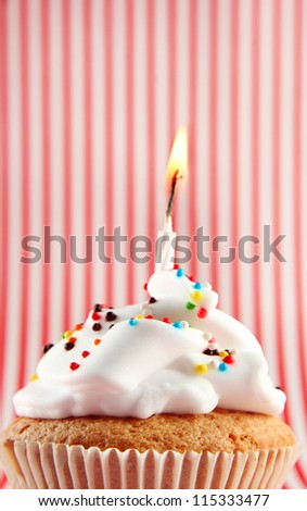 tasty birthday cupcake with candle, on red-white striped background - stock photo