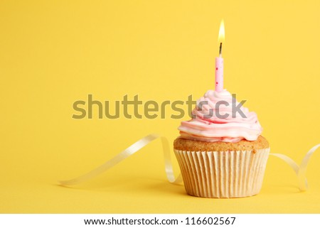 tasty birthday cupcake with candle, on yellow background - stock photo