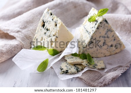 Tasty blue cheese with basil on paper - stock photo