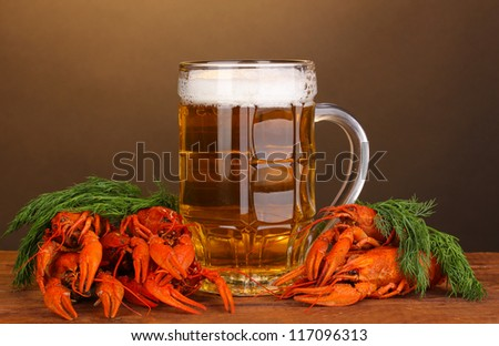 Tasty boiled crayfishes and beer on table on brown background - stock photo
