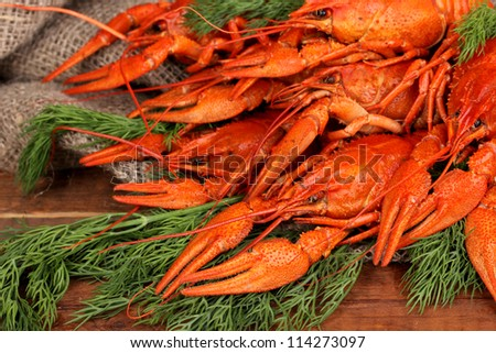 Tasty boiled crayfishes with fennel on table on sackcloth background - stock photo