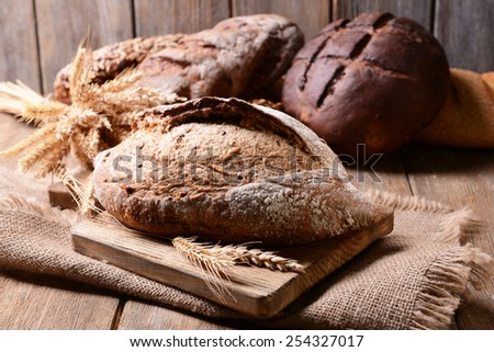 Tasty bread on table on wooden background - stock photo