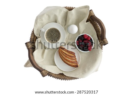 Tasty breakfast for one on a rustic wicker tray with a cup of fresh espresso coffee, boiled egg, ramekin of fresh assorted berries and a crispy pastry viewed from above isolated on white - stock photo