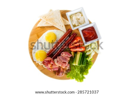 Tasty breakfast - fried eggs, sausages and meat on wooden board - stock photo