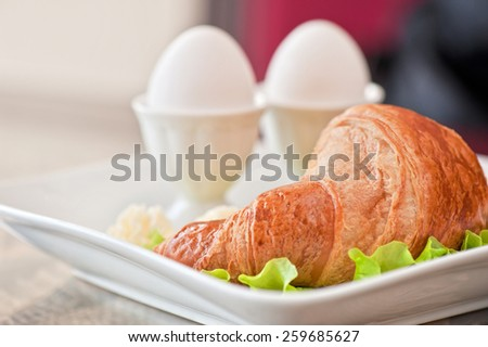 Tasty breakfast from eggs and croissant - stock photo