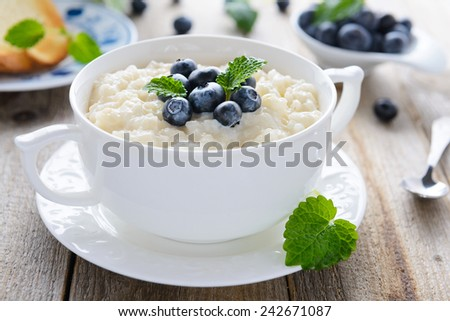 Tasty breakfast: rice pudding with blueberry - stock photo
