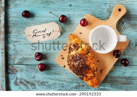 Tasty breakfast with fresh croissant, empty cup of coffee, cherries and notes on a wooden table, selective focus on croissant - stock photo