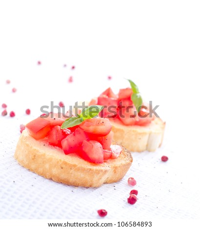 Tasty bruschetta with bread tomatoes basil and white space - stock photo