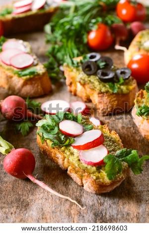 Tasty bruschettas with pesto sauce and radish,selective focus  - stock photo
