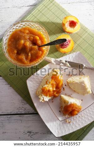 tasty bun with homemade jam on wooden table - stock photo