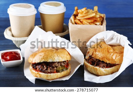 Tasty burger and french fries on wooden table background , close-up Unhealthy food concept - stock photo
