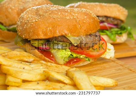 Tasty burger with melted cheese and a thick succulent ground beef patty garnished with lettuce, tomato, onion and rocket on a sesame bun standing on a picnic table in the garden - stock photo