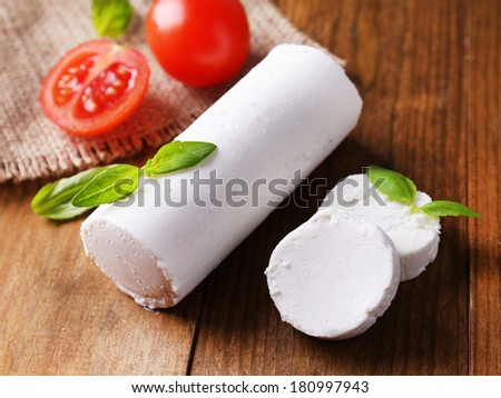 Tasty bushe cheese with basil and tomato, on wooden table - stock photo