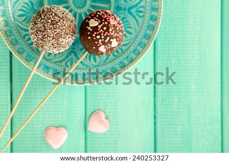 Tasty cake pops on plate, on wooden table - stock photo