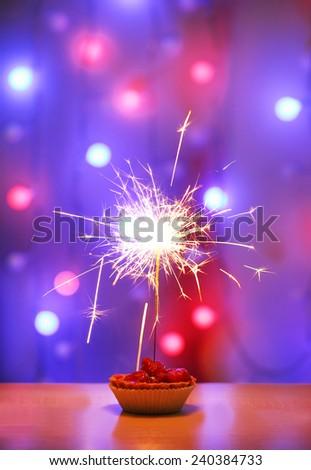 Tasty cake with sparkler on shiny background - stock photo