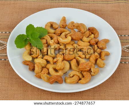 tasty cashew nuts with leaves in the dish on the mat. - stock photo