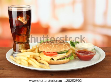 Tasty cheeseburger with fried potatoes and cold drink, on bright background - stock photo