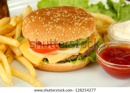 Tasty cheeseburger with fried potatoes, on bright background - stock photo