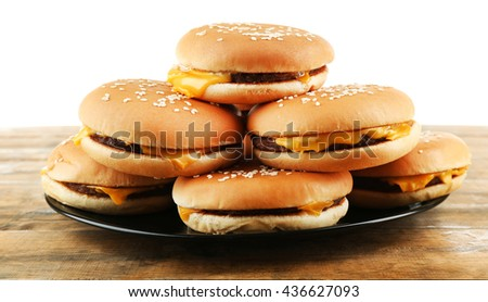 Tasty cheeseburgers on plate, isolated on white - stock photo
