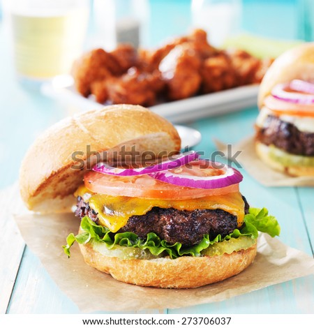 tasty cheeseburgers with wings and beer - stock photo