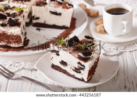 Tasty cheesecake with pieces of chocolate cookies close-up and coffee on the table. horizontal