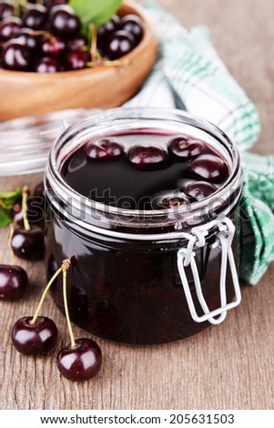 Tasty cherry jam in glass jar on wooden table - stock photo
