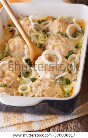 Tasty chicken balls baked with cheese and onions close up in baking dish. vertical - stock photo