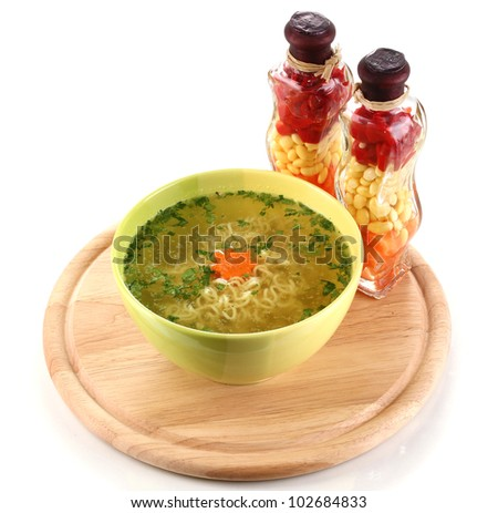 Tasty chicken stock with noodles on wooden round board isolated on white - stock photo