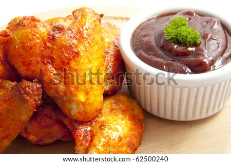 Tasty chicken with red sauce on wooden plate - stock photo