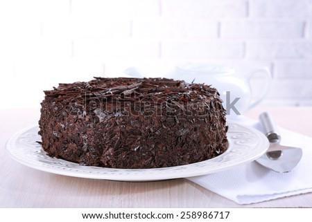 Tasty chocolate cake on table on brick wall background - stock photo