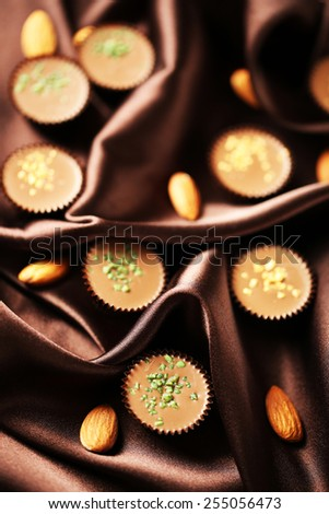 Tasty chocolate candies on satin cloth, close up - stock photo