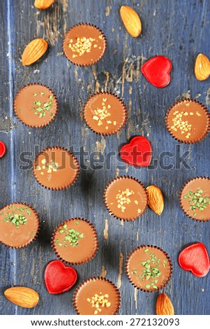 Tasty chocolate candies with almond and hearts on wooden table - stock photo