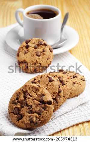Tasty chocolate cookies and cup of coffee on white napkin - stock photo