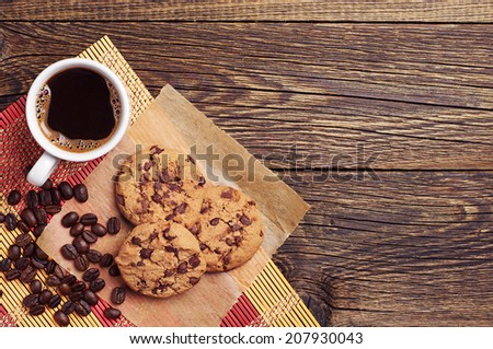 Tasty chocolate cookies and cup of coffee on wooden background. Top view - stock photo