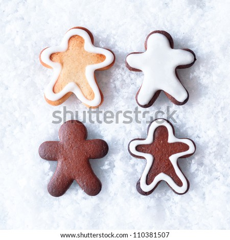 Tasty Christmas gingerbread men cookies with decorative icing lying on a bed of snow with copyspace - stock photo