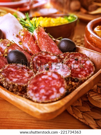 Tasty cold cuts on wooden table at home, slices of salami, pieces of pepperoni and ham, festive menu, different kind of smoked meat - stock photo