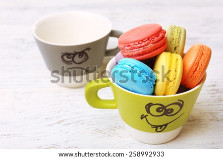 Tasty colorful macaroons and cups on color wooden background - stock photo