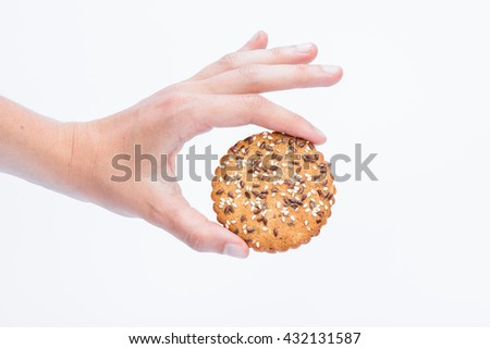 Tasty cookie with sesame and flax seeds between women hand fingers, isolated with white background   - stock photo
