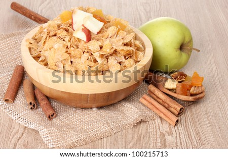 tasty cornflakes in bowl with dried fruits, glass of milk and apple on wooden table - stock photo