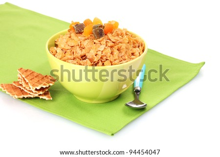 tasty cornflakes in bowl with dried fruits on green napkin - stock photo