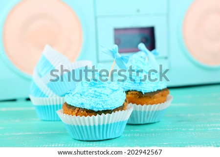 Tasty cup cakes with cream on blue wooden table - stock photo
