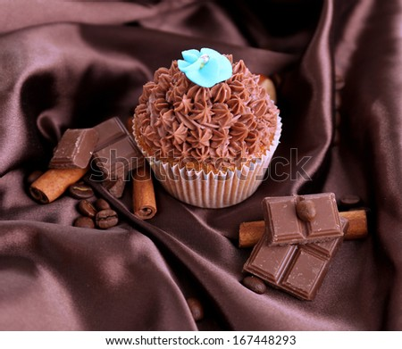 Tasty cupcake with butter cream, on color fabric background - stock photo