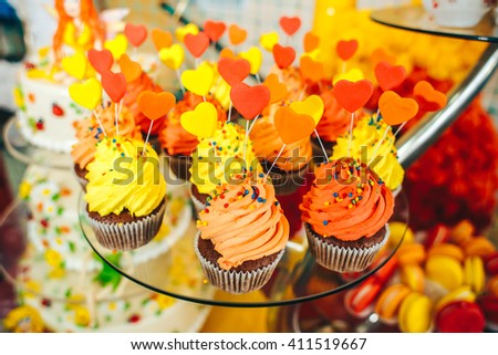Tasty cupcakes decorated with heats. Decoration for wedding or happy birthday celebration. Selective focus - stock photo