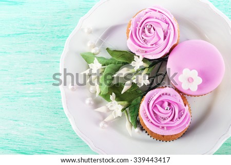 Tasty cupcakes on plate, on color wooden background - stock photo