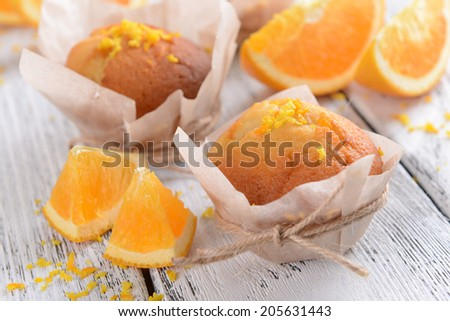 Tasty cupcakes with orange on table close-up - stock photo