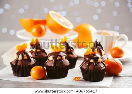 Tasty cupcakes with slice of mandarin and chocolate on a paper over light wooden background - stock photo