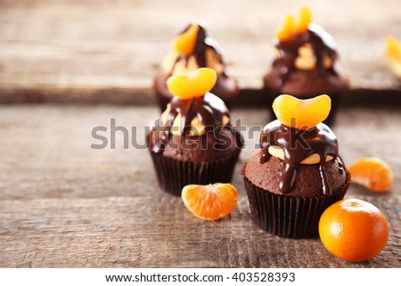 Tasty cupcakes with slice of mandarin and chocolate on wooden background - stock photo
