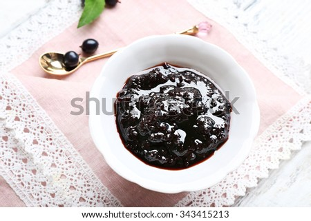 Tasty currant jam with berries on table close up - stock photo