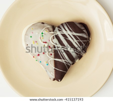Tasty decorative gingerbread heart on the yellow plate. Sweet food. Tasty cookie. - stock photo