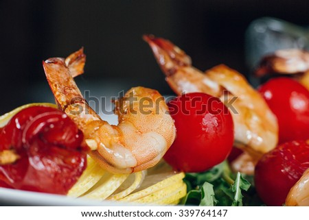 Tasty delicious shiny shrimps prawns grilled with tomatoes cherry on a skewer served on plate with lemons, vegetables and salad. Professional studio shooting for cafe restaurant. Dish, appetizer, food - stock photo